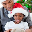Happy little girl playing with a Christmas gift with her father — Stock Photo