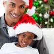 Afro-American dad and daughter wearing a Christmas hat - Stockfoto
