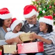 Afro-American family holding Christmas gifts — Stock Photo