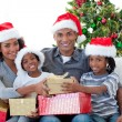 Smiling Afro-American family sharing Christmas presents — 图库照片