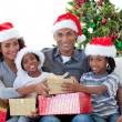 Smiling Afro-American family sharing Christmas presents — Stock Photo