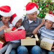 Happy Afro-American family playing with Christmas presents — Stockfoto