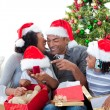 Happy Afro-American family having fun with Christmas presents — Stockfoto