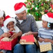 Happy Afro-American family opening Christmas presents — 图库照片