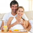 Smiling couple having breakfast lying in the bed — Stock Photo
