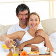 Romantic couple having breakfast lying in the bed — Stock Photo