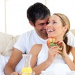 Beautiful couple having breakfast lying in the bed — Stock Photo