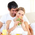 Caucasian couple having breakfast lying in the bed — Stock Photo