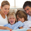 Jolly family reading a book on bed — Stock Photo #10293355