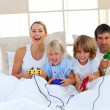 Loving family playing video game in the bedroom — Stock Photo #10293357