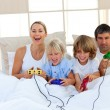Stock Photo: Loving family playing video game in the bedroom