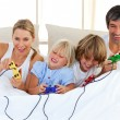 Stock Photo: Adorable family playing video game in the bedroom