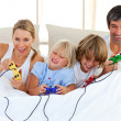 Adorable family playing video game in the bedroom — Stock Photo