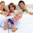 Little blond girl playing video game with her family — Stock Photo