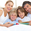 Smiling family reading a book on bed — Stock Photo