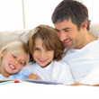 Close-up of father and his children reading book — Stock Photo