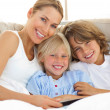 Stock Photo: Attractive mother and her children reading book