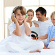 Happy little boy listening music sitting on bed — Stock Photo