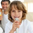 Little boy singing with a microphone - Stock Photo