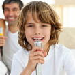 Stock Photo: Little boy singing with microphone