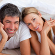 Enamoured couple having fun lying on bed — Stock Photo #10293449