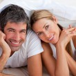 Stock Photo: Enamoured couple having fun lying on bed