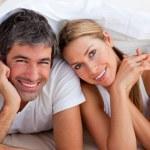 Enamoured couple having fun lying on bed — Stock Photo
