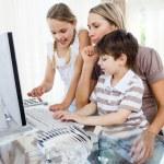 madre attenta, insegnando ai suoi figli come usare un computer — Foto Stock