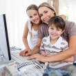 Caring mother and her children at a computer — Stock Photo #10293469