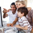 Children learning how to use computer with their parents — Foto de stock #10293477