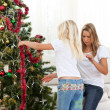 Blond little girl and her mother decorating Christmas tree - Stockfoto