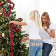 Blond little girl and her mother decorating Christmas tree - Stock Photo