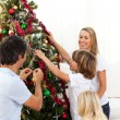 Joyful family decorating Christmas tree - Stockfoto