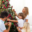 Happy family decorating Christmas tree - Foto Stock