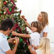 Happy family decorating Christmas tree - Stockfoto