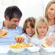 Joyful family eating hamburgers — Stock Photo #10293527