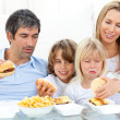 Merry family eating hamburgers — Stock Photo