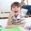 Close-up little boy drawing lying on the floor — Stock Photo