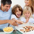 Excited children eating a pizza with their parents — Stock Photo