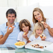 Smiling family eating a pizza sitting on the floor — Stock Photo