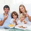 Stock Photo: Smiling family eating pizzsitting on floor