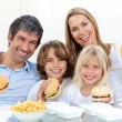 Happy family eating hamburgers sitting on the floor — Stock Photo