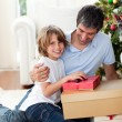 Little boy opening Christmas gifts with his father - Stockfoto