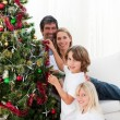 Parents and their children decorating a Christmas tree — Stock Photo