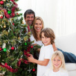 Happy family decorating a Christmas tree with baubles — Stock Photo