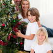 Portrait of a happy family decorating a Christmas tree — Stock Photo #10293582