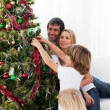Smiling family hanging decorations on a Christmas tree — Stock Photo