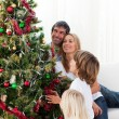 Happy family decorating a Christmas tree — Stock Photo #10293584