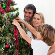 Little boy hanging Christmas decorations with his parents — Stock Photo #10293587