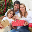 Happy family holding Christmas gifts — Stock Photo